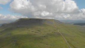 Ένα εναέριο μπροστινό μήκος σε πόδηα ενός δύσκολου βουνού κορυφών με την πράσινη πορεία κλίσεων και ιχνών κάτω από έναν μεγαλοπρε απόθεμα βίντεο