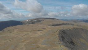 Ένα εναέριο μπροστινό μήκος σε πόδηα ενός σκωτσέζικου οροπέδιου συνόδου κορυφής με τον τεράστιο απότομο βράχο στο υπόβαθρο φιλμ μικρού μήκους