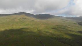 Ένα εναέριο μπροστινό μήκος σε πόδηα μιας μεγαλοπρεπούς χλοώδους κλίσης κορυφών βουνών με μια πορεία ιχνών, έναν μπλε ουρανό και  απόθεμα βίντεο