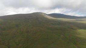 Ένα εναέριο μπροστινό μήκος σε πόδηα μιας μεγαλοπρεπούς χλοώδους κλίσης κορυφών βουνών με μια πορεία ιχνών, έναν μπλε ουρανό και  φιλμ μικρού μήκους
