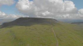 Ένα εναέριο οπίσθιο μήκος σε πόδηα ενός δύσκολου βουνού κορυφών με την πράσινη πορεία κλίσεων και ιχνών κάτω από έναν μεγαλοπρεπή απόθεμα βίντεο
