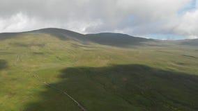 Ένα εναέριο οπίσθιο μήκος σε πόδηα μιας μεγαλοπρεπούς χλοώδους κλίσης κορυφών βουνών με μια πορεία ιχνών, έναν μπλε ουρανό και έν απόθεμα βίντεο