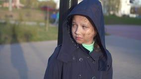 Ένα ενοχλητικό πορτρέτο ενός έφηβη με μια ατέλεια ή ενός προσώπου εγκαυμάτων στην οδό με μια κουκούλα απόθεμα βίντεο