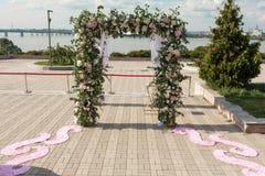 Ένα εορταστικό chuppah που διακοσμείται με τα φρέσκα όμορφα λουλούδια για μια υπαίθρια γαμήλια τελετή στοκ φωτογραφία