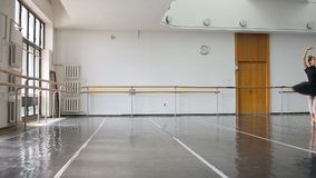 Ένα επαγγελματικό ballerina σε ένα μαύρο πακέτο χορεύει σε μια μεγάλη αίθουσα κατάρτισης απόθεμα βίντεο