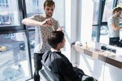 Ένα επαγγελματικό hairstylist με μια χτένα και ψαλίδι στο χέρι του που ορίζει την υγρή μαύρη και κοντή τρίχα του ατόμου στο α στοκ εικόνα