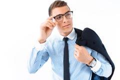 Ένα επιτυχές άτομο στα γυαλιά και ένα κοστούμι κρατά ένα σακάκι άνω του s του στοκ εικόνα
