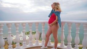 Ένα επιτυχές έγκυο πρότυπο στέκεται σε ένα μαγιό στο μπαλκόνι και την τοποθέτηση απόθεμα βίντεο