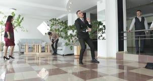 Ένα επιχειρησιακό άτομο έχει τη διασκέδαση στην αίθουσα ενός σύγχρονου γραφείου απόθεμα βίντεο