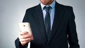 Ένα επιχειρησιακό άτομο σε ένα κοστούμι με έναν δεσμό κρατά ένα κινητό τηλέφωνο μοντέρνη εμφάνιση, κομψότητα απόθεμα βίντεο