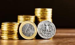 Ένα ευρο- νόμισμα και εμείς νόμισμα δολαρίων τετάρτων και χρυσά χρήματα Στοκ εικόνες με δικαίωμα ελεύθερης χρήσης