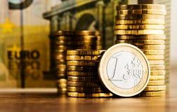 Ένα ευρο- νόμισμα και χρυσά χρήματα στο γραφείο Στοκ Εικόνα