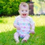 Ένα ευτυχές γελώντας μωρό σε μια ζωηρόχρωμη συνεδρίαση φανέλλων στη χλόη Στοκ φωτογραφία με δικαίωμα ελεύθερης χρήσης