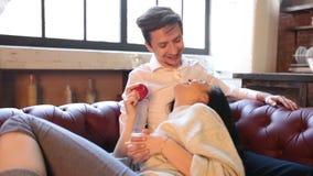 Ένα ευτυχές ζεύγος αστειεύεται πρίν έρχεται σε σεξουαλική επαφή στον καναπέ στο καθιστικό στο σπίτι, μια γυναίκα που κλίνει σε έν απόθεμα βίντεο