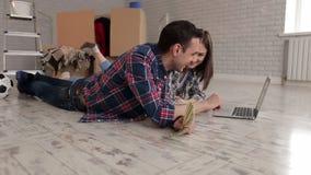 Ένα ευτυχές ζεύγος στα πουκάμισα καρό βάζει στο πάτωμα σε ένα νέο διαμέρισμα με ένα lap-top φιλμ μικρού μήκους