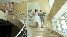 Ένα ευτυχές ζεύγος των newlyweds κατεβαίνει τα κομψά σκαλοπάτια στο ξενοδοχείο απόθεμα βίντεο