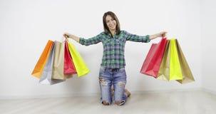 Ένα ευτυχές κορίτσι κρατά πολλές χρωματισμένες τσάντες με τις αγορές στα χέρια που στέκονται στα γόνατα στο πάτωμα στο σπίτι απόθεμα βίντεο