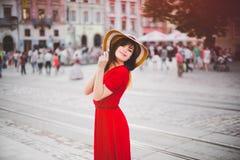 Ένα ευτυχές κορίτσι σε ένα κόκκινο φόρεμα στο πόλη-κέντρο Στοκ Εικόνες