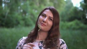 Ένα ευτυχές κορίτσι στέκεται σε ένα δάσος με το θερινό ηλιόλουστο καιρό Πορτρέτο απόθεμα βίντεο