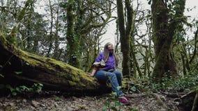 Ένα ευτυχές κορίτσι στο περιστασιακό ύφος κάθεται στο βρύο-καλυμμένο δέντρο και ανατρέχει σε ένα δάσος πυξαριού απόθεμα βίντεο
