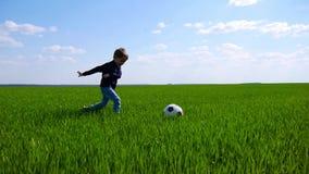 Ένα ευτυχές παιδί κλωτσά ευτυχώς μια σφαίρα ποδοσφαίρου και τρέχει πέρα από έναν τομέα της πράσινης χλόης σε σε αργή κίνηση απόθεμα βίντεο