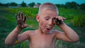 Ένα ευτυχές παιδί παρουσιάζει χέρια του βρώμικα από τη γη και τα γέλια, ένα αγόρι που λερώνεται στη λάσπη, ένα εύθυμο χόμπι παιδι απόθεμα βίντεο