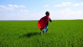 Ένα ευτυχές παιδί σε ένα κοστούμι superhero σε ένα κόκκινο ακρωτήριο και σε μια μάσκα τρέχει στην πράσινη χλόη μια ηλιόλουστη ημέ φιλμ μικρού μήκους