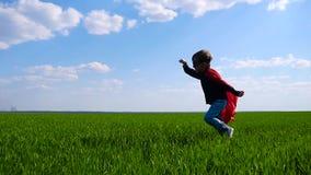 Ένα ευτυχές παιδί σε ένα κοστούμι superhero τρεξίματα στα κόκκινα επενδυτών πέρα από έναν πράσινο τομέα φιλμ μικρού μήκους
