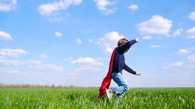 Ένα ευτυχές παιδί σε ένα κοστούμι superhero τρεξίματα στα κόκκινα επενδυτών πέρα από έναν πράσινο τομέα μια ηλιόλουστη ημέρα, ενά απόθεμα βίντεο