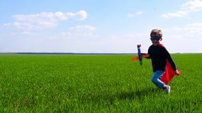 Ένα ευτυχές παιδί στα τρεξίματα superhero κοστουμιών πέρα από την πράσινη χλόη, που κρατά ένα αεροπλάνο, ενάντια σε έναν νεφελώδη απόθεμα βίντεο