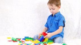 Ένα ευτυχές προσχολικό παιδί κάθεται σε έναν καναπέ και χτίζει από τους χρωματισμένους φραγμούς του σχεδιαστή Παιχνίδια των παθητ απόθεμα βίντεο