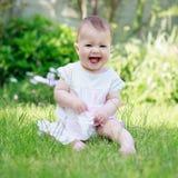 Ένα ευτυχές χαμογελώντας μωρό σε μια συνεδρίαση φορεμάτων σε μια χλόη Στοκ Εικόνες