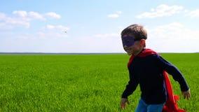 Ένα ευτυχές χαρούμενο παιδί σε ένα κοστούμι superhero, έναν κόκκινο επενδύτη και μια μάσκα, τρέχει πέρα από έναν πράσινο τομέα κα απόθεμα βίντεο