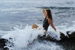 Ένα ευτυχές όμορφο μακρυμάλλες κορίτσι σε ένα μαύρο μαγιό κάθεται σε έναν βράχο σε έναν αφρό του ψεκασμού θάλασσας Στοκ Εικόνες