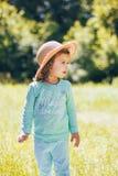 Ένα ευτυχές όμορφο μικρό κορίτσι στα ενδύματα μεντών και καπέλο αχύρου στον ηλιόλουστο τομέα υπαίθρια στοκ φωτογραφίες με δικαίωμα ελεύθερης χρήσης