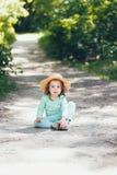 Ένα ευτυχές όμορφο μικρό κορίτσι στα ενδύματα μεντών και καπέλο αχύρου στο ηλιόλουστο θερινό δάσος υπαίθρια στοκ εικόνες