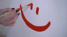 Ένα ευτυχές smiley σε ένα παιδιάστικο ύφος, ένας καλλιτέχνης κοριτσιών χρωμάτισε ένα χαμόγελο σε έναν άσπρο καμβά απόθεμα βίντεο