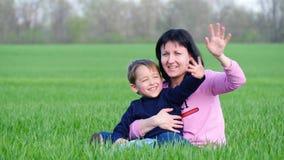 Ένα ευτυχείς παιδί και μια μητέρα κάθονται στην πράσινη χλόη στο πάρκο, κυματίζοντας ευτυχώς τα χέρια τους φιλμ μικρού μήκους
