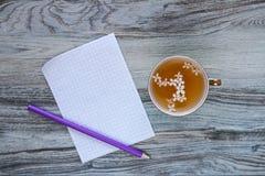 Ένα ευώδες βοτανικό τσάι βιταμινών με τα άσπρα ιώδη λουλούδια και ένα φύλλο του καθαρού άσπρου ελεγμένου εγγράφου με ένα πορφυρό  Στοκ Εικόνες