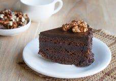 Ένα εύγευστο κομμάτι του κέικ σοκολάτας σε ένα άσπρο πιάτο Στοκ Εικόνες