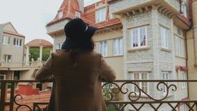 Ένα εύθυμο κορίτσι σε ένα μακρύ παλτό φορά ένα μαύρο μοντέρνο καπέλο έφθασε για πρώτη φορά στην Ευρώπη, κύματα το χέρι της στους  απόθεμα βίντεο