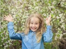 Ένα εύθυμο κορίτσι σε ένα πουκάμισο τζιν αύξησε τα χέρια της επάνω στον οπωρώνα κερασιών στοκ εικόνες