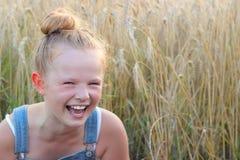 Ένα εύθυμο μικρό κορίτσι σε έναν τομέα σιταριού Στοκ Εικόνα
