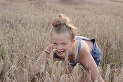 Ένα εύθυμο μικρό κορίτσι σε έναν τομέα σιταριού Στοκ Εικόνες