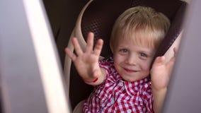 Ένα εύθυμο μωρό που κυματίζει το χέρι του καθμένος σε ένα κάθισμα αυτοκινήτων παιδιών ` s απόθεμα βίντεο