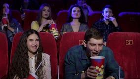 Ένα εύθυμο νέο ζεύγος ρίχνει popcorn στον κινηματογράφο απόθεμα βίντεο