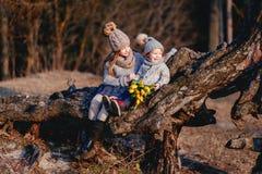 Ένα εύθυμο χαριτωμένο μικρό παιδί με την κόκκινη τρίχα που κρατά τις κίτρινες τουλίπες έξω την πρώιμη άνοιξη στο δάσος κοντά στο  στοκ εικόνες