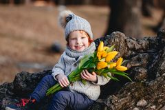 Ένα εύθυμο χαριτωμένο μικρό παιδί με την κόκκινη τρίχα που κρατά τις κίτρινες τουλίπες έξω την πρώιμη άνοιξη στο δάσος κοντά στο  στοκ φωτογραφίες
