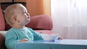 Ένα ελκυστικό αγόρι 2 χρονών τρώει μια σαλάτα κόκκινων τεύτλων Το πρόσωπο είναι λερωμένο με το κουάκερ Κάθεται στον πίνακα φιλμ μικρού μήκους