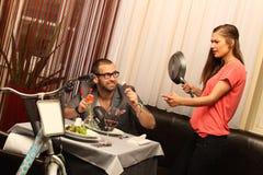 Ένα ελκυστικό καυκάσιο ζεύγος που έχει ένα γεύμα με το κρασί στο εστιατόριο με ένα ποδήλατο Στοκ Φωτογραφία